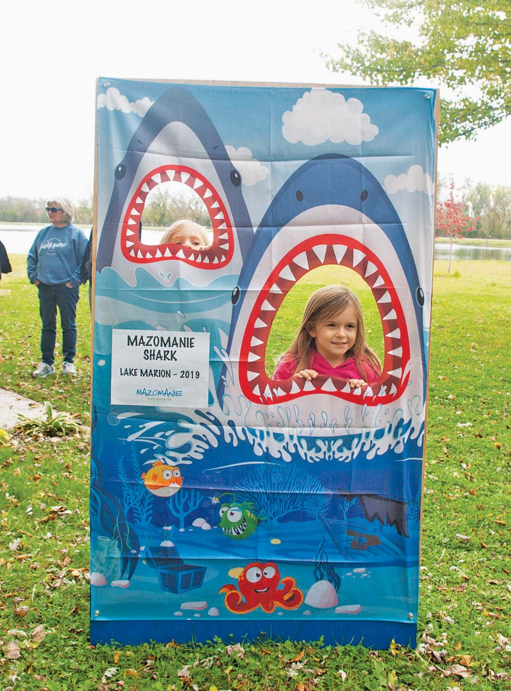 Lucy, above, just barely peeks through, and Trinity Beil is all smiles, as they impersonated the infamous Lake Marion shark at the grand opening Saturday, Oct. 19. Despite the rain Mazomanie residents gathered for food and beer to dedicate the lake's long-awaited restoration.