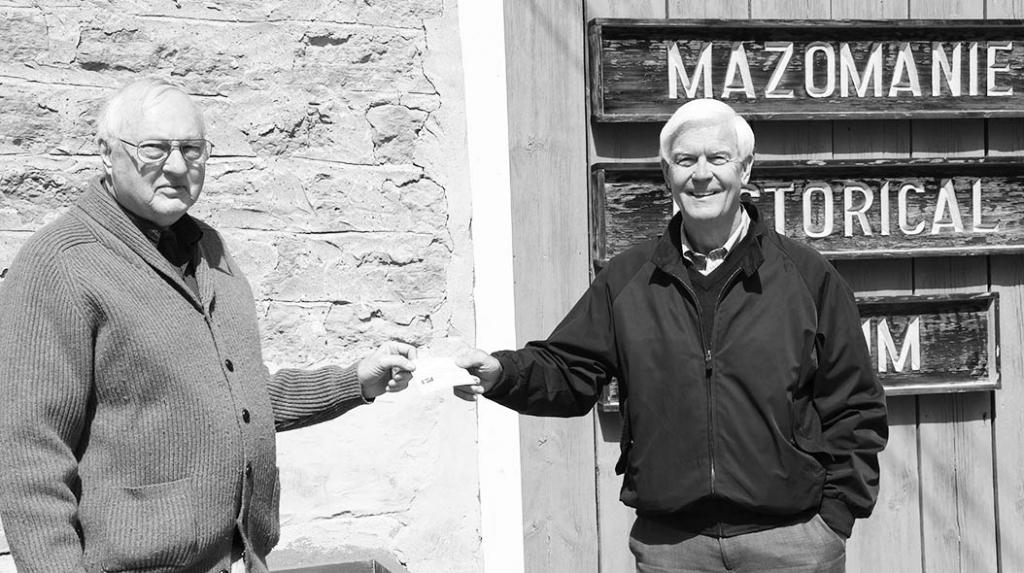Bob Dodsworth, Mazomanie Historical Society board member, hands Gary Harrop, President of the Village of Mazomanie, a check for $16,000 raised by a...